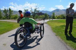 A man uses a recumbent cycle on a trail while others walk and skateboard in the distance