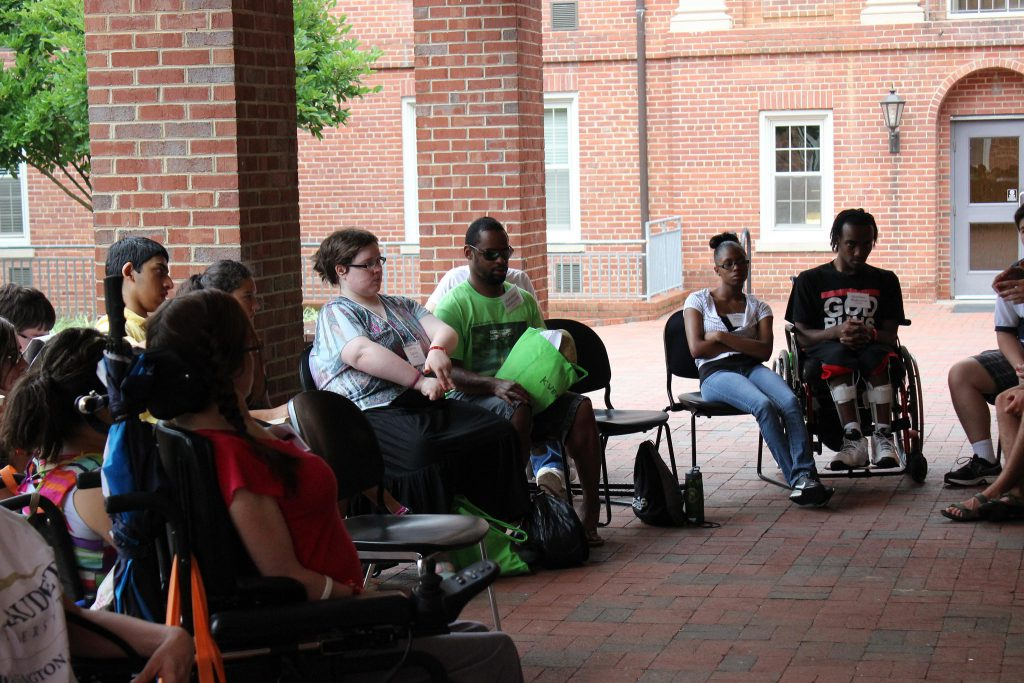 a group of people with disabilities sit in a circle talking