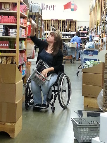 A woman in a wheelchair with a shopping basket in her lap reaches up for a box on a shelf.