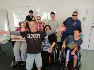 A group of youth with different disabilities laugh and smile while posing together