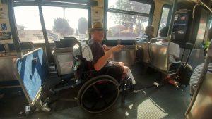 A man using a wheelchair rides on a public bus.