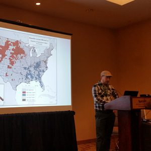 Conference presentation showing speakers and slide behind with map of the USA