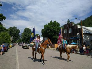 Two girls ride horses in a parade through town. They both hold flags.
