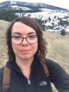 Ari Lissau. A woman with brown hair stands outside with snow-covered hills in the background. She is wearing a black shirt, glasses, and a backpack.