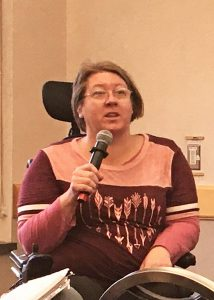 Bonnie Kelly speaks into a microphone. She is a wheelchair user.