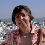headshot of Dr. von Reichert. She is an older woman with short, gray/brown hair, wearing a pink striped shirt. She is standing outside, and there is a view overlooking a city and ocean behind her.