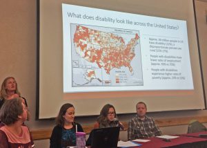 Kelly, Troutman, Greiman, and Myers sit in the front of a room presenting. There is a slide projected above their heads with a map of disability rates across the U.S. Greiman speaks into a microphone.