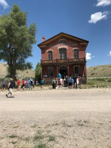 A historic building in a ghost town. People walk in front of building and up the stairs to get inside.