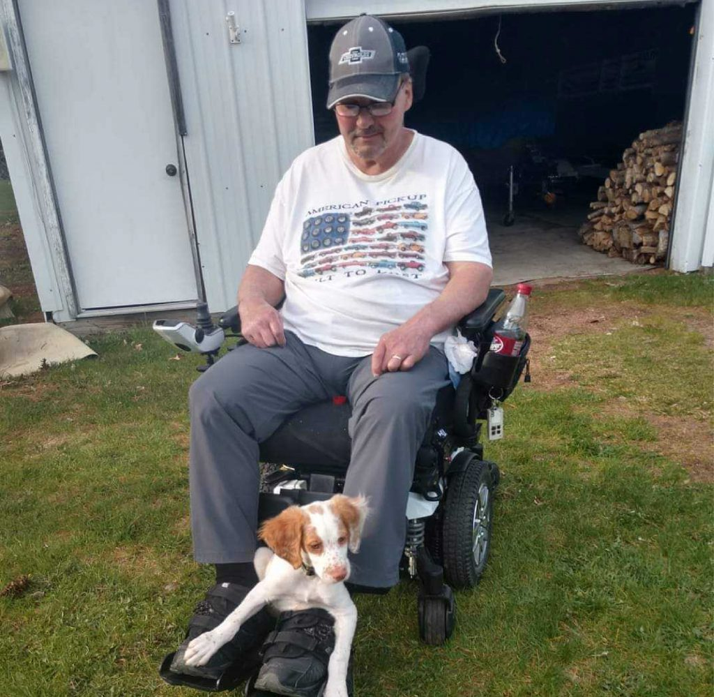Greg English using a power wheelchair, while wearing a hat. A white and brown dog rests on his feet.