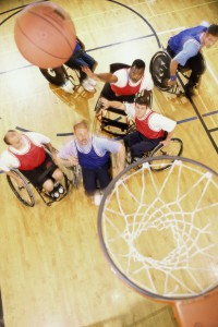 group of adult men in wheelchairs playing basketball (79073915)