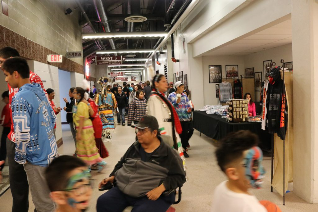 People walking past vendor tables at an indoor powwow.