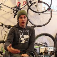 Joe Stone talking and gesturing during an interview, sitting in front of several bikes hanging on the wall