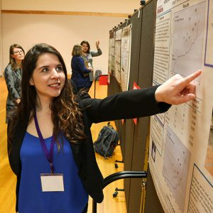 Student pointing to her research poster, in the poster hall at a conference.