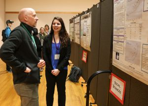 Megan Miller discusses her research during her poster presentation.