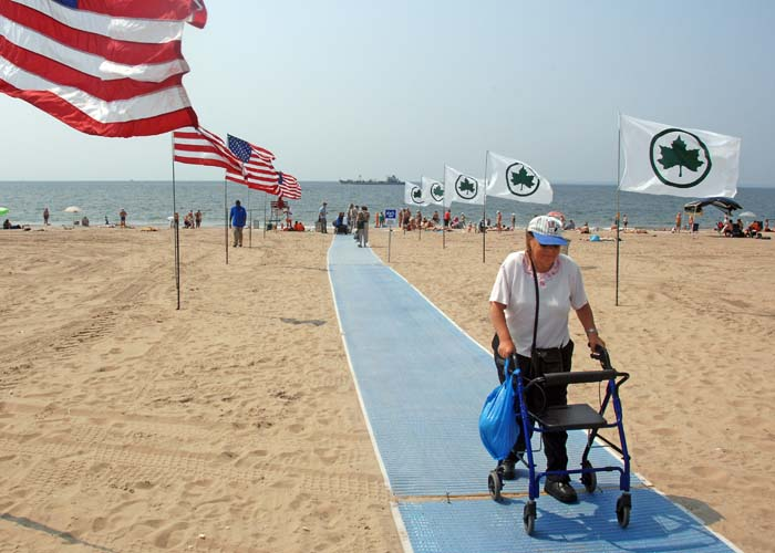 A woman using a walker walks down an accessible surface on the beach between two rows of flags.