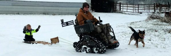 A man using a power wheelchair pulls a young boy on a sled th rough the snow. A dog runs in front of them.