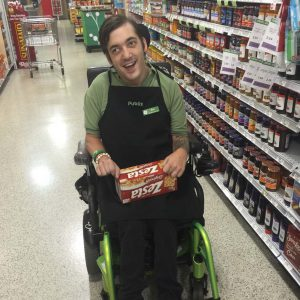 A man using a wheelchair working at a grocery store.