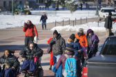 A group of people, some with visible disabilities, gather outside in the winter to advocate for disability rights. Some are using wheelchairs and other mobility devices, and everyone is bundled up in winter coats, hats, and gloves.