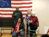 Four people with visible and invisible disabilities stand in front of a disability rights flag.