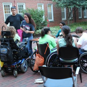 A group of seven people, three sitting in wheelchairs, at a workshop outside around a table