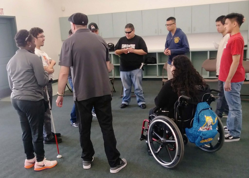 A group of people in a circle in a room. One person is using a wheelchair, one person is using a cane to help with navigation, and the others are standing unaided.