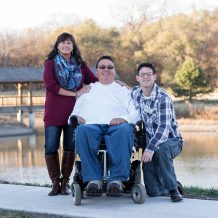 A three-person family poses for the camera with mother, father using a wheelchair and son.