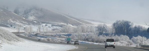 Cars driving on a highway through snow-covered hills.