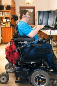 A man using a power chair works on a computer at a raised computer desk.