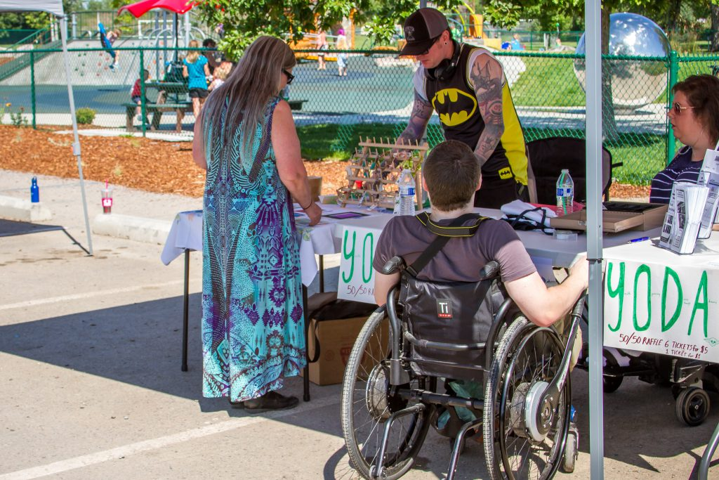 Two people, one in a wheelchair, visit a booth at an outdoor event.