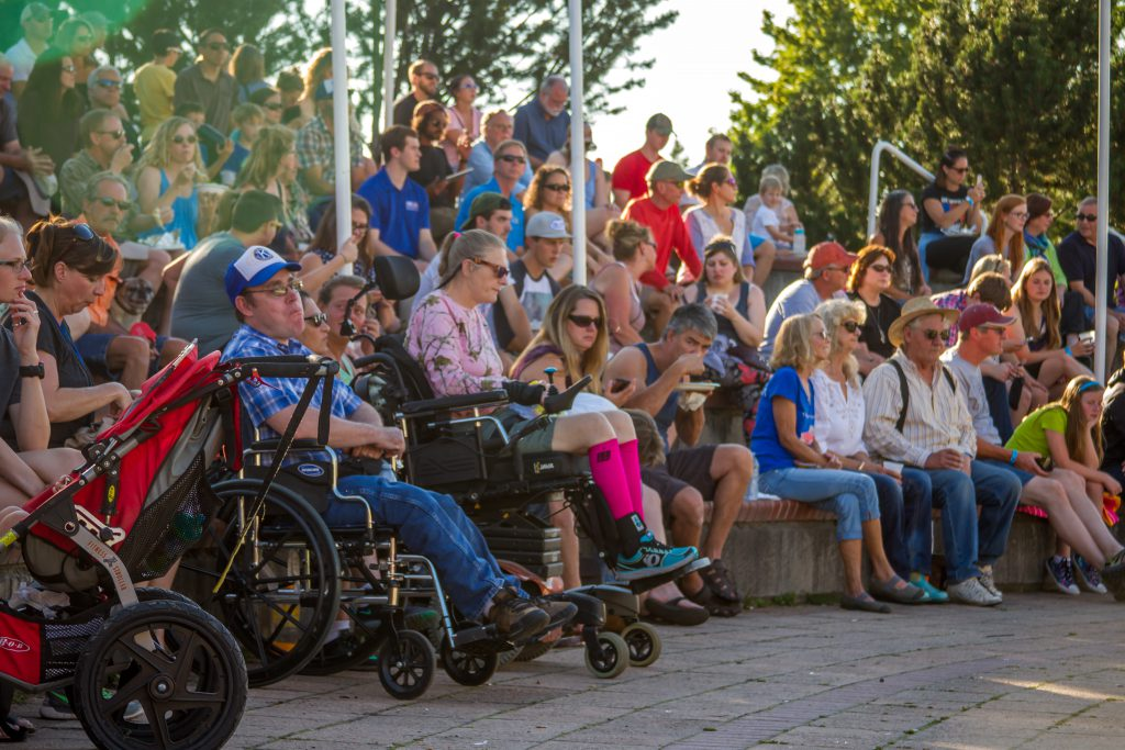 A large group of people seated in a small outdoor arena. In the front row are people using wheelchairs and power chairs, and a person with a stroller for their baby.
