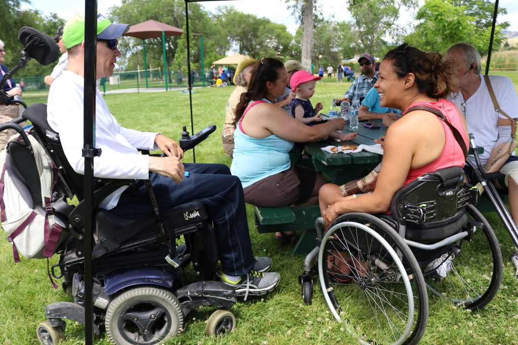 A group of people gathered around a picnic table in a park. Some of them are using wheelchairs, and one man is an amputee.