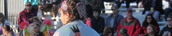 Woman dancing at a pow-wow wearing traditional dress