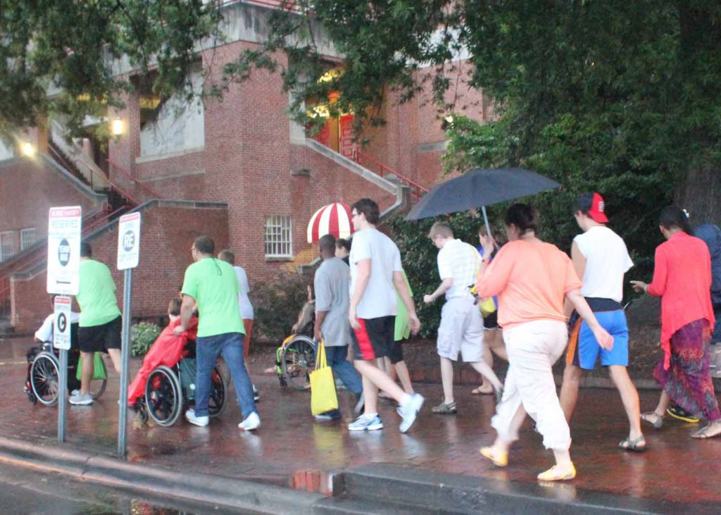 A group of people, some using wheelchairs, move down the sidewalk in the rain.