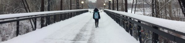 A person walks on a snowy bridge that has sort-of been plowed.