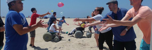 a group of people with various disabilities on a beach throwing water balloons to eachother