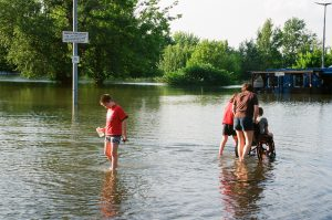 two people push a person in a wheelchair through a flooded street