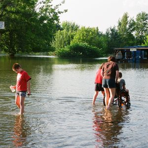 People walk through a flooded area. One person is being pushed in a wheelchair. The water is ankle deep.