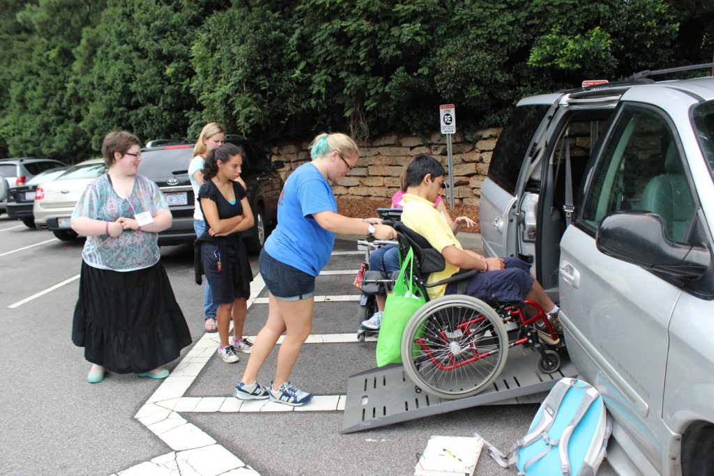 A person assists another person using a wheelchair into an accessible van.