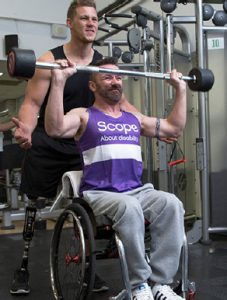 A man with a prosthetic leg spots a man in a wheelchair lifting weights